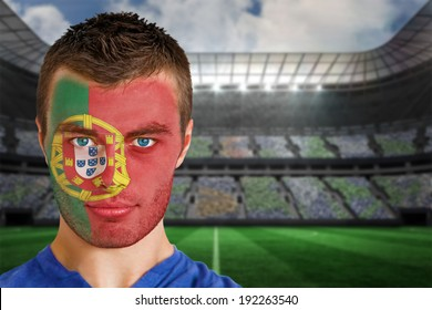 Composite image of portugal football fan in face paint against large football stadium under spotlights