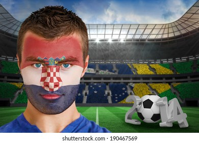 Composite image of serious young croatia fan with face paint against large football stadium