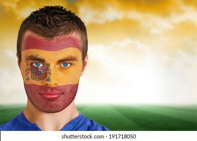 Composite image of spain football fan in face paint against football pitch under yellow sky