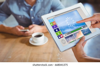Composite image of various video and computer icons against person using tablet computer in cafe