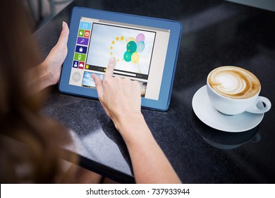 Composite image of various video and computer icons against woman having coffee and using her tablet