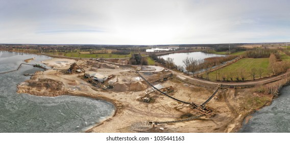 Composite panorama of aerial photographs and aerial photos of a wet quarry for gravel and sand with an almost frozen lake and large machines for excavation and processing, made with drone