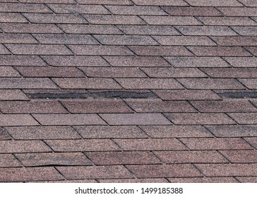Composite shingles damaged on roof by storm with strong winds.