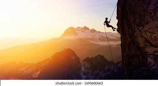 Composite. Silhouette Rappelling from Cliff. Beautiful aerial view of the mountains during a colorful and vibrant sunset or sunrise. Landscape taken in British Columbia, Canada. Concept: Adventure