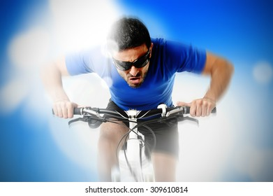 composite of young aggressive sport man riding mountain bike in frontal view and suffering face expression surrounded by lights and lens flare on a blue background in energy and strength concept