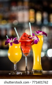 Composition with 3 yellow and red cocktails and orchid flowers on the blurred background. Focus om red cocktail