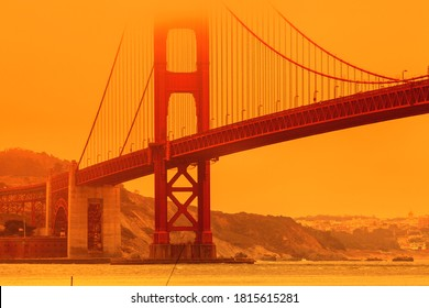 Composition about wildfires and climate change concept. Bottom view of smoky orange sky on Golden Gate bridge of San Francisco city from lime point. California fires in United States.