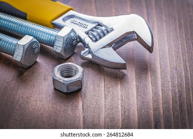 composition of adjustable wrench bolts and nut on vintage wooden board construction concept
