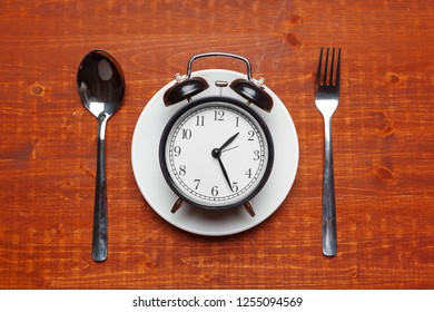 composition with alarm clock, plate and utensils