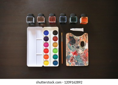 Composition of artistic objects, palette, brush, watercolor paintings, box of watercolors, oil painting