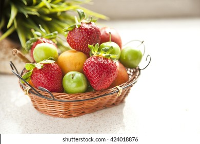 Composition with assorted fruits in wicker basket with daylight