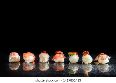 Composition of assorted Nigiri sushi with different fish and shrimp placed in row on black background