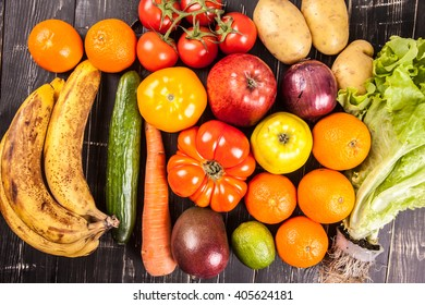 Composition with assorted raw organic vegetables on black wooden background