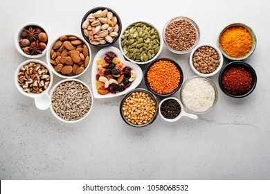 Composition with assortment of superfood products in bowls on gray background, top view