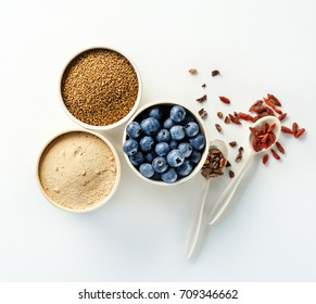 Composition with assortment of superfood products in bowls and spoons on white background, top view
