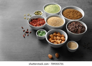 Composition with assortment of superfood products in bowls on grey table