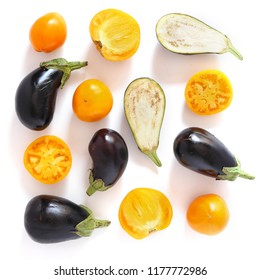 Composition of aubergine and chopped yellow tomatoes, top view, flat layout.