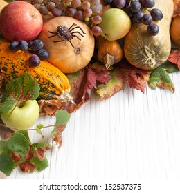 Composition of autumn pumpkins with apple and grapes on the wooden background
