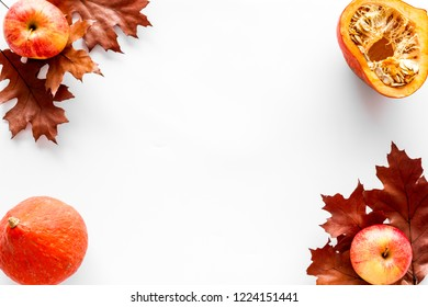 Composition with autumn vegetables and leaves in red and orange colors. Brown dried leaves, pumpkin, apple on white background top view copy space