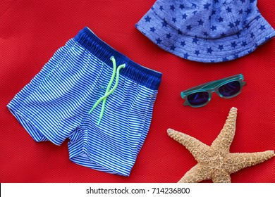 Composition with baby swimming trunks on red background