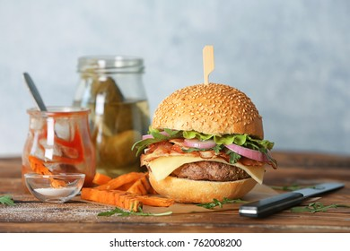 Composition with bacon burger on wooden table