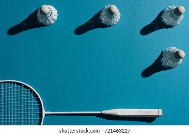 composition with badminton racket and shuttlecocks placed on blue surface