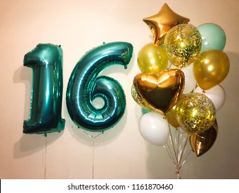 Composition of balloons of gold, white, transparent with confetti, gold stars and hearts, as well as large numbers 16