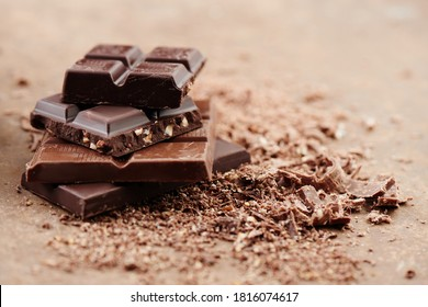 Composition of bars and pieces of different milk and dark chocolate, grated cocoa on a brown background side view close up