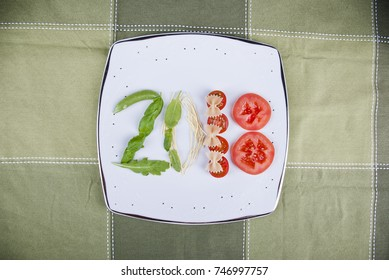 A composition of basil, arugola, pasta and tomatoes on a plate which make a 2018 number.