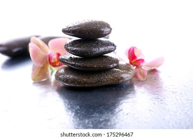 Composition with beautiful blooming orchid with water drops and spa stones, on light background