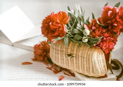 composition with beautiful fresh flowers red peonies in a wicker bag, and a cup of tea with a book on a white sofa