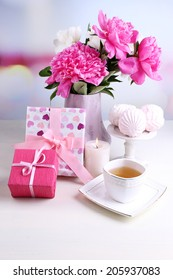 Composition of beautiful peonies in vase, tea in cup and marshmallow, on table, on light background