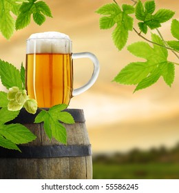 Composition of beer in glass with barrel and hop plant