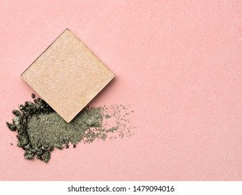 Composition of beige and green shimmering eyeshadow on pale pink background. Creative image of decorative cosmetics samples. Smudged cosmetic products. Beauty and makeup concept.