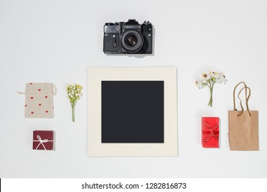 Composition with black photo frame, retro camera, red gift boxes, craft bag, canvas bag with red heart shapes and spring field flower on white background. Trendy flat lay mockup for bloggers