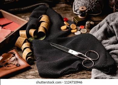 Composition of black polka-dotted fabric with scissors, sewing spools, tape measure and colorful buttons with glasses placed on rough wooden table