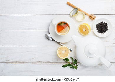 Composition of black tea with lemon, honey and mint on a white background.top view.