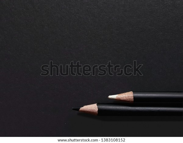 A composition of black and white pencils on black background