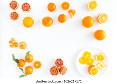 Composition of blood oranges, oranges and  clementines whole, halved, peeled, and sliced arranged on marble board, porcelain plate and white background. Top view.