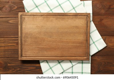 Composition of board and napkin on wooden background