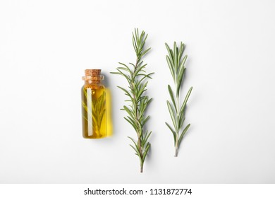 Composition with bottle of rosemary oil on white background, top view