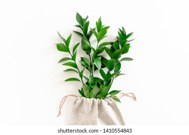 Composition with bouquet of ruscus in canvas bag on white background