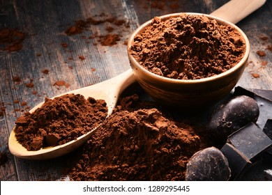 Composition with bowl of cocoa powder on wooden table.