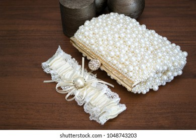 Composition of a bridal garter and purse decorated with artificial pearls