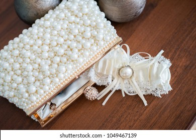 Composition of a bridal garter and purse decorated with imitation pearls