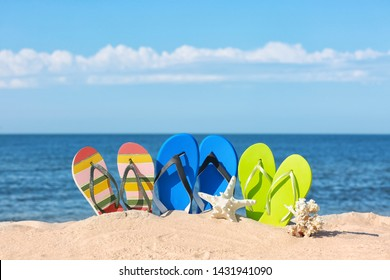 Composition with bright flip flops on sand near sea in summer. Beach accessories