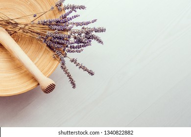 Composition of a bunch of smelling lavander flower and pestles on a wooden round plate on white wooden background top view.