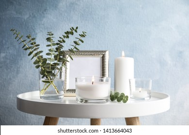 Composition with burning aromatic candles on table near color wall