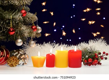 a composition of burning candles and ornaments in the snow. background wooden panel and branches of fir-tree. Color photo