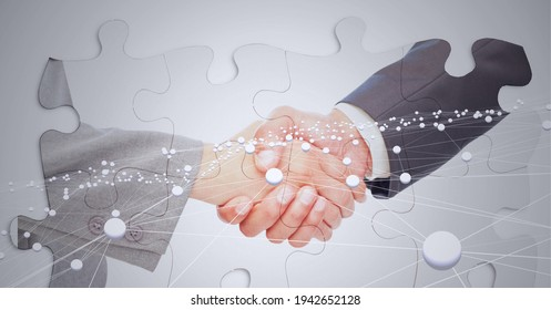 Composition of businessman and businesswoman shaking hands with network of connections and puzzles. global business, finances and networking concept digitally generated image.